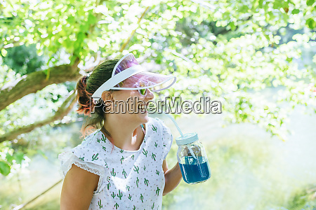laughing woman drinking blue drink in