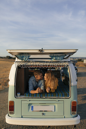 young couple lying in camper van