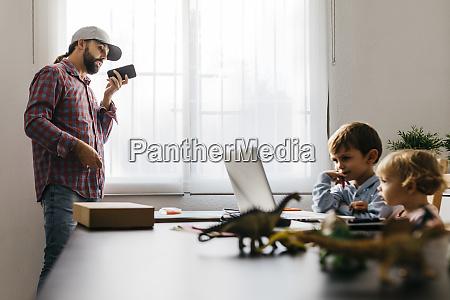 father recording audio file while children