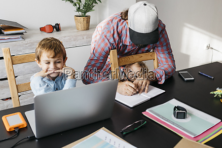 father writing in notebook while children