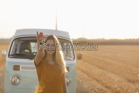 happy young woman holding car key