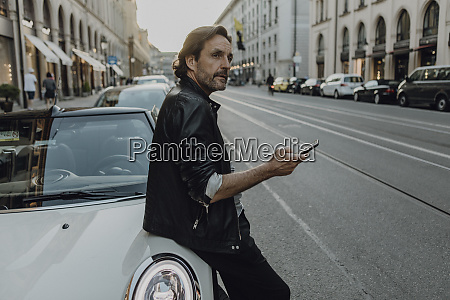 mature man leaning on car holding