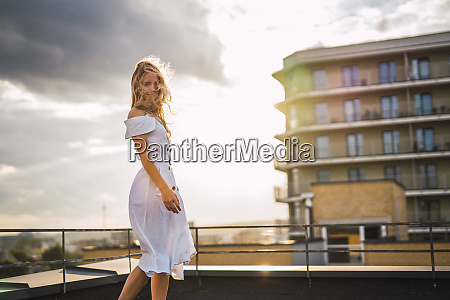 blond young woman standing on roof