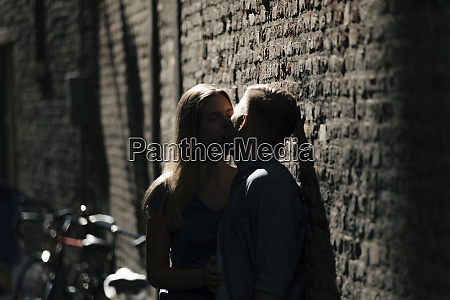 affectionate young couple kissing at brick