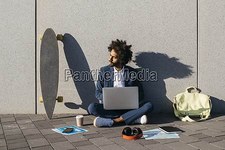 young businessman sitting outdoors at a