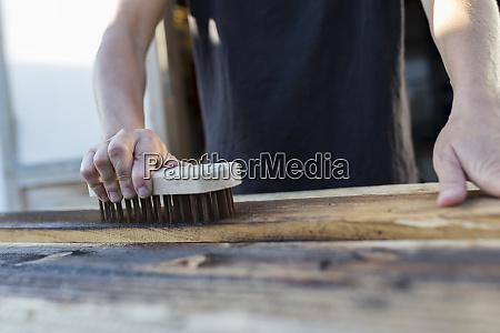 handwerker mit pinsel auf stueck holz