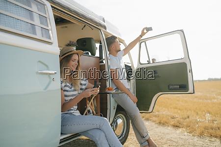 junges ehepaar mit handys entspannt sich