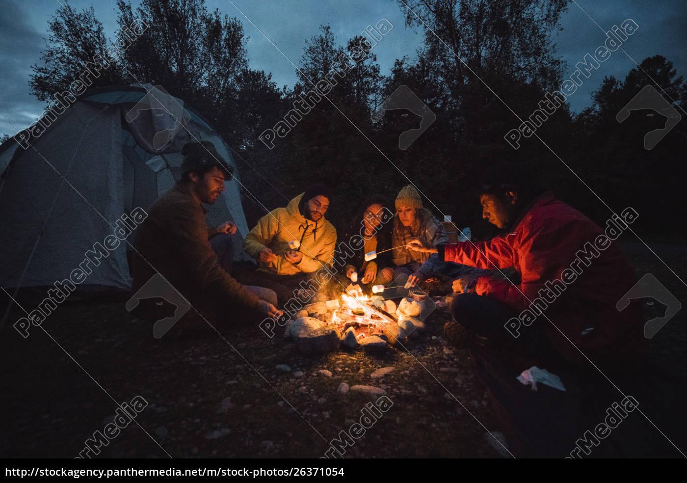 gruppe, von, freunden, sitzen, am, lagerfeuer, rösten - 26371054