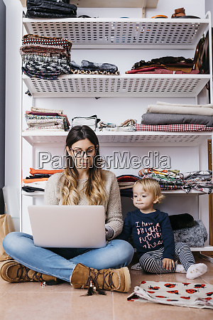 llittle daughter watching mother sitting on