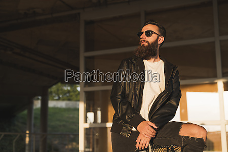 stylish bearded young man outdoors looking