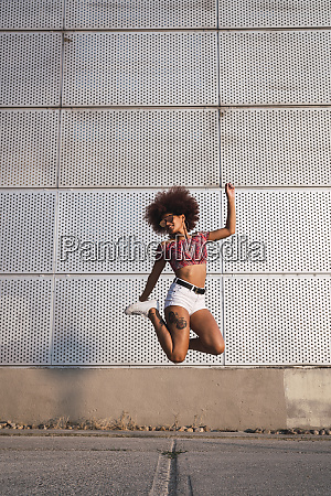 fashionable young woman jumping in the