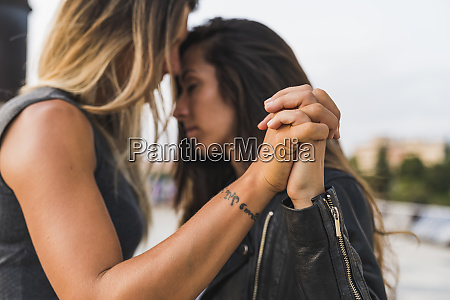 affectionate lesbian couple holding hands outdoors