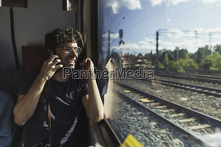 happy man traveling by train talking