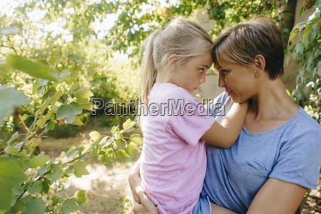 mother carrying daughter in garden