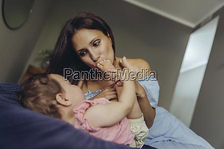 mother kissing her baby girls feet