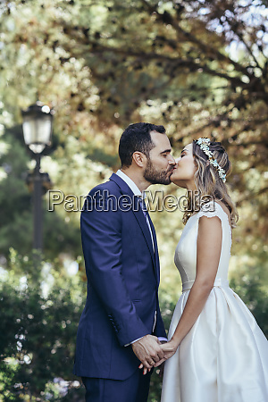 happy bridal couple kissing in a