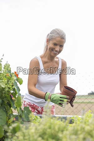 portrait of smiling woman gardening at