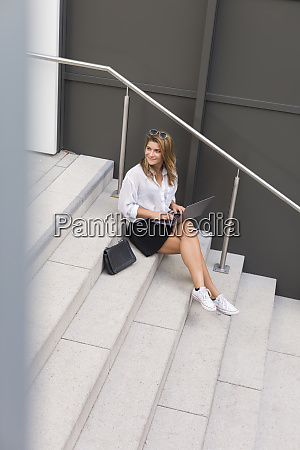 smiling businesswoman sitting on stairs using