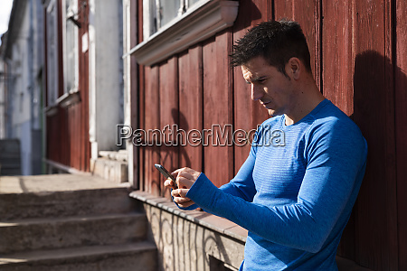 athlete leaning against house wall using