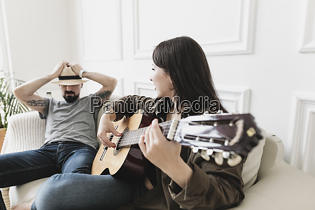 relaxed couple sitting on couch woman