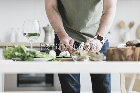 man preparing salad at home partial