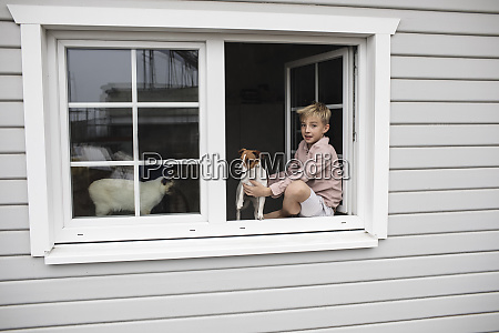 portrait of boy sitting on window