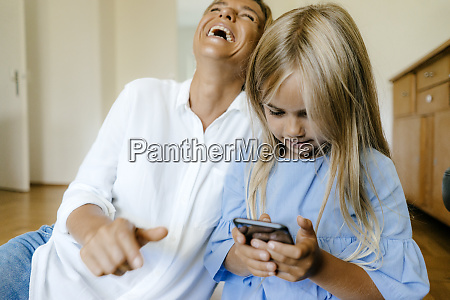 laughing mother and daughter looking at