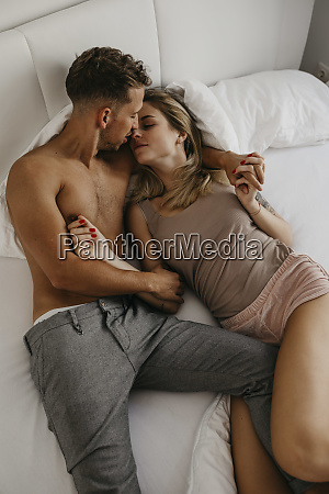 romantic young couple kissing in bed