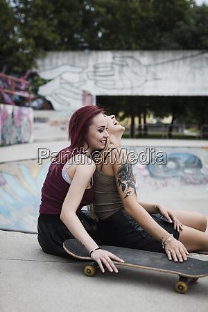 happy friends sitting in skatepark
