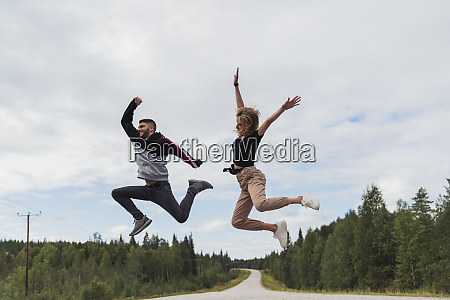 finland lapland exuberant young couple jumping