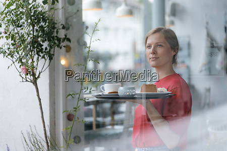 young woman serving coffee and cake