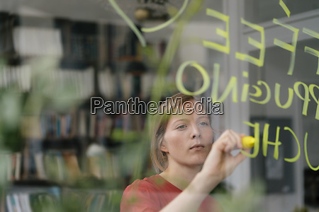 young woman writing offer on windowpane