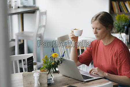 young woman using laptop at table