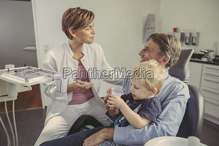 female dentist talking to patient with