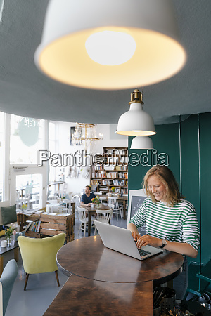 smiling young woman using laptop in