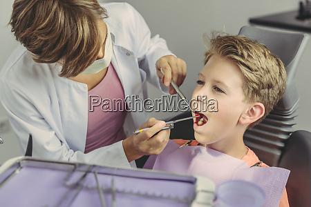 dentist examining boys teeth with dental