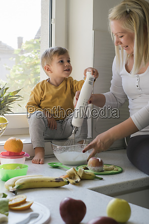 mother and little son whisking cream