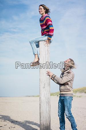 mature man helping woman to climb