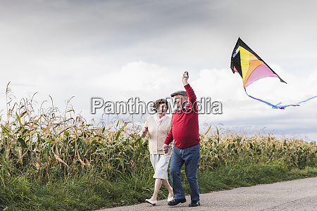happy senior couple with kite in