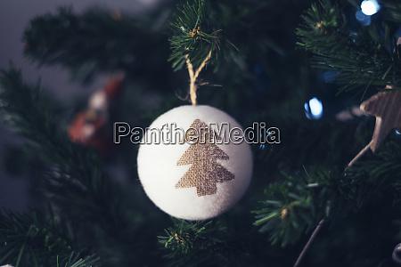 christbaumstein haengt am weihnachtsbaum