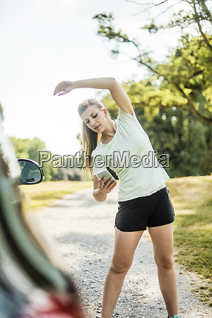 sportive young woman stretching and using