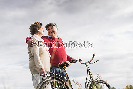 happy senior couple with bicycles embracing