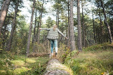 little girl balancing on a tree