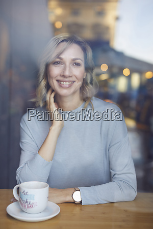 blond woman in cafe behind window