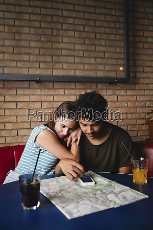 affectionate young couple sitting at table