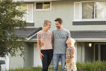 smiling parents with boy standing in