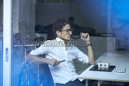 pensive young man behind windowpane sitting