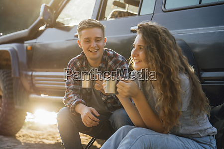 young couple sitting by car taking