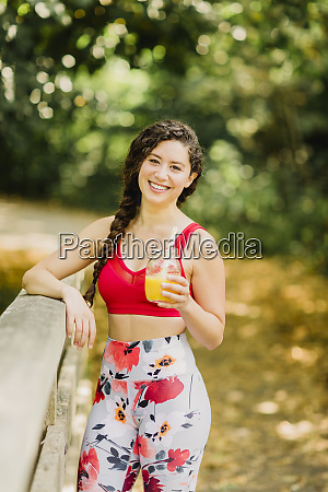 young woman drinking juice after practicing