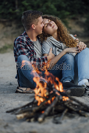 romantic couple sitting at a campfire
